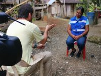 Juan Miguel Álvarez interviewing Afro-Colombian leader Elizabeth Moreno Barco in Cucurrupí, Colombia, on the banks of the San Juan River, while residents from the place watch.
