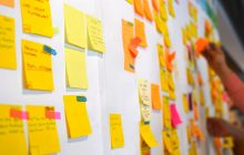 A white board covered in yellow and orange post-it notes.