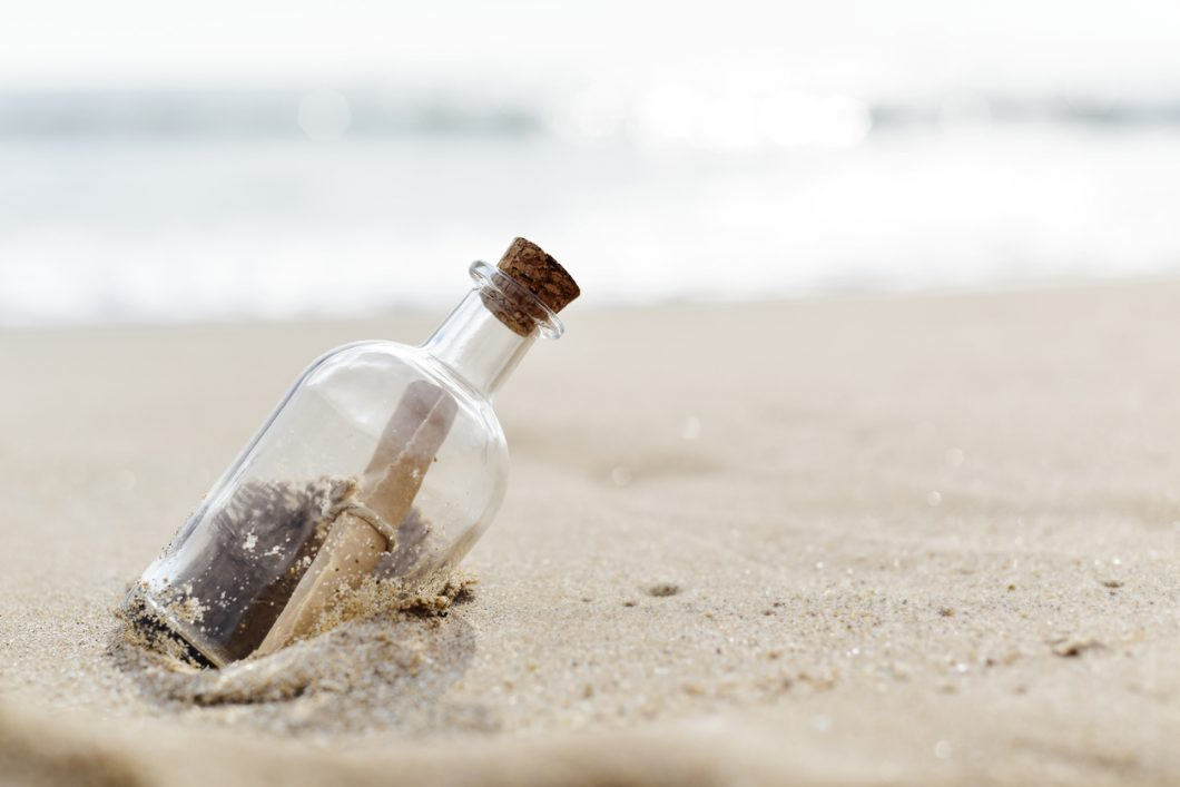 Message in a bottle, resting on sand